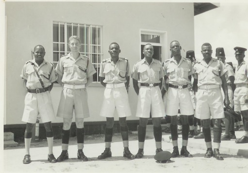 Instructional Staff outside Stores – ZP Mobile Unit – Kamfinsa – Circa 1967 L-R (as viewed): Stores Sub Insp; Paul RUSSELL; Sub Insp.Mwanamane; Sgt Chingunya; Sgt. ? ; Sgt. Sub Insp. ? Recruits in background